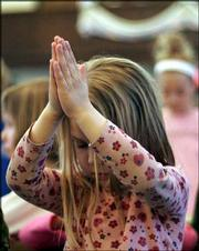 Emily Walthall, a kindergartner at St. John's Catholic School, offers up a prayer Friday during a special Mass of Remembrance for Pope John Paul II.