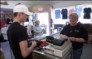 Lori Devins, right, rings out Jesse Ridder at Extreme Christian Clothing, 938 Mass.