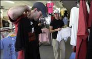 Justin Hurd, left, and Jesse Ridder shop for T-shirts at Extreme Christian Clothing on Tuesday.