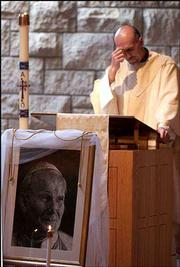 A picture of Pope John Paul II rests in front of Father James Sanchez as he reads the Gospel at the Saturday afternoon Mass at St. Lawrence Catholic Campus Center.