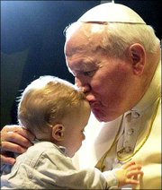 Pope John Paul II kisses an unidentified baby at the end of a general weekly audience in the Pope Paul VI Hall at the Vatican, Wednesday, March 14, 2001.