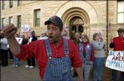 Mike Capra takes part in a pro-troop rally in this March 2003 file photo. Two Lawrence printers have linked Capra to a campaign postcard that suggests City Commission incumbent David Schauner was involved in domestic abuse.