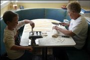 Donna Mader cuts and presses homemade dough for noodles with her young assistant, Bryce Druessel, the son of her son's fiance. They're sitting on blue naugahyde upholstery installed by the Clutter family.