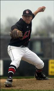 Lawrence High's Daren Parker unleashes a pitch against Shawnee Mission East. The Lions won, 6-5 in eight innings, Tuesday at Ice Field.