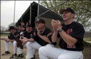 Lawrence High baseball coach Brad Stoll, right, cheers as the Lions score in the second inning. LHS beat Shawnee Mission East, 6-5 in eight innings, Tuesday at Ice Field.
