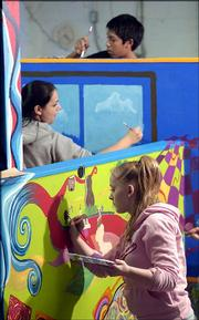 From top, Van Go Mobile Arts participants Denzel Clendon, 14, Sara Zangeneh, 16, and Tiffany Luthi, 15, paint a CASA house project Tuesday for the 14th annual benefit for the Douglas County agency. Van Go Mobile Arts is donating its time to paint the house constructed by Clovis Construction and designed by Sabatini Architects Inc. Van Go has kicked off a fund-raising drive to add space to its facility at 715 N.J.