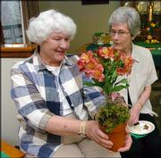 Meadowlark Garden Club members Dorothy Curnes, left, and Virginia Curran look over an arrangement created by Hy-Vee floral manager Cindy Goldring. The club heard a presentation from Goldring at its monthly meeting on Tuesday.