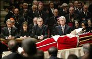 From left, President George W. Bush, Laura Bush, former presidents George H.W. Bush and Bill Clinton, and Secretary of State Condoleezza Rice kneel by the body of late Pope John Paul II Wednesday inside St. Peter's Baslica at the Vatican.