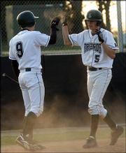 The Firebirds' Jake Hoover (9) congratulates Anthony Dreiling after Dreiling scored a run in the fourth inning. The Firebirds toppled the Lions, 8-3, Thursday evening at FSHS.