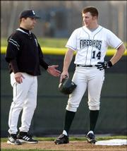 Free State high baseball coach Mike Hill, left, chats with Firebird base runner Brett Lisher. The Firebirds beat Lawrence High, 8-3, Thursday night at Free State Field.