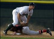 Free State High third baseman Cory Cooper attempts to tag out Lawrence High base runner Travis Hart.