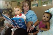 Marietta Winfrey, center, owner of Little Lambs Daycare, center, reads to, from left, Jackson Nichols, 2, Cassidy Dunn, 1, and Breckin Younger, 1, during story time. Little Lambs, which is run from Winfrey's home, looks after 10 children on a daily basis.