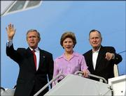 President Bush and first lady Laura Bush, joined by Bush's father, former President George H.W. Bush, wave as they step down from Air Force One in Waco, Texas. They arrived Friday after flying from Rome, where they attended the funeral of Pope John Paul II, and will stay at their ranch in nearby Crawford, Texas, before a meeting there Monday with Israeli Prime Minister Ariel Sharon.