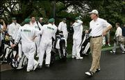 Golfer Ernie Els walks past caddies gathered in front of the clubhouse after rain suspended play Friday at Augusta National in Augusta, Ga. The golfers will attempt to play the second and third rounds today, weather permitting.