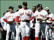 Boston Red Sox captain Jason Varitek, center, walks with teammates after receiving their World Series rings prior to the start of their 8-1 victory over New York.