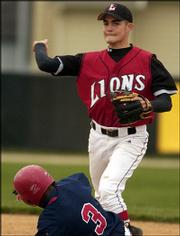 Lawrence High's Will Falk turns a double play as Olathe North's Josh Gore tries to break it up at second base. Falk hit a home run and earned the pitching victory in relief as the Lions rallied for a 14-13 victory Tuesday at Ice Field.