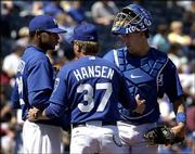 Kansas City starter Denny Bautista, left, and catcher John Buck, right, listen to pitching coach Guy Hansen during the fourth inning of the Royals' 10-2 loss to Seattle. The Mariners completed a sweep of their series with the Royals on Thursday at Kauffman Stadium in Kansas City, Mo.