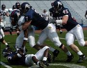 KU defenders Charles Gordon (3), Nick Reid (7) and Kevin Kane (45) gang up to tackle running back Nick Kurtenbach.