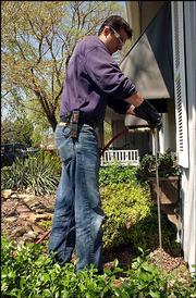 Vanja Mehmedovic, a technician for Haley Pest Control of Lawrence, sinks an applicator into the ground to treat a home in southwest Lawrence for termites. Termites often swarm at this time of year, leading to busy days for pest control companies.