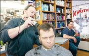 Jon Amyx cuts a man's hair while Amyx's son, Jay, waits for a customer at the Downtown Barber Shop, 824 Mass.