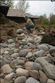Kansas Insurance Commissioner Sandy Praeger tinkers with stones in her recently installed dry creek bed. The faux stream adds beauty to Praeger's yard but also solves a drainage problem.