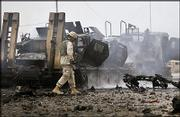 A U.S. soldier passes by destroyed Army vehicles after a bomb exploded near a U.S. convoy in an area of Baghdad, Iraq, setting a U.S. oil tanker on fire Wednesday. No casualties were reported.