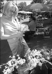 LORA STOPPEL, Lawrence, picks out some tuberosas to buy in September at the Lawrence Farmers Market.