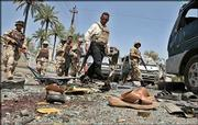 Iraqi soldiers examine wreckage left in the wake of a car bomb in Baghdad, Iraq. A series of attacks hit Baghdad's Azamiyah section Friday, including car bombs and a mortar round, killing at least 13 Iraqis and wounding 50, officials said.