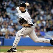 Toronto's Roy Halladay delivers against New York. Halladay pitched a three-hitter in the Blue Jays' 2-0 victory over the Yankees on Friday night in New York.