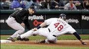 Cleveland's Travis Hafner (48) slides safely into third base under the tag of Kansas City's Tony Graffanino. The Indians beat the Royals, 6-0, Friday night in Cleveland.
