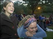 Laura Adams, a Kansas University senior from Overbrook, left, and Maggie Beedles, Lawrence, right, watch a musical performance by Shannon Murray during the annual Womyn Take Back The Night march. The Friday night event included poetry readings, live music and a candlelight march from Buford M. Watson Jr. Park to South Park.