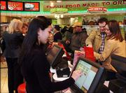 """Megan Reimer, of Hollidaysburg, Pa., uses a touch screen to order a sub sandwich at the Sheetz Convenience Restaurant in Altoona, Pa. This 10,000-square-foot store by Sheetz Inc., an Altoona-based company, features a dining room, free wi-fi Internet access and a cold """"grab and go"""" counter with yogurt, fresh fruit, ready made vegetable trays and salads."""