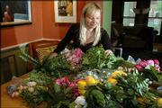 "Cherie Yvette, who sells flowers from a cart in downtown Lawrence, is starting ""Do-It-Yourself Weddings,"" so brides and their bridal parties can put together their own corsages and bouquets. Yvette unpacks a shipment of fresh roses, herbs and other greenery Thursday."