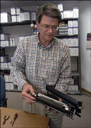 John Ross, owner of Laser Logic, displays the inner workings of a printer cartridge. Ross says that his company has grown during its 15 years of business.