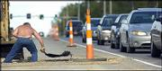 Traffic backs up along Sixth Street near Wakarusa Drive as Richard Taylor, Perry, with Hamm Asphalt, shovels asphalt into a cutout in the roadway. Construction throughout Lawrence has slowed the flow of traffic, and snarls will continue until summer's end. Taylor laid asphalt over new storm sewer lines on Tuesday.
