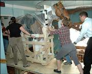 The preserved body of Comanche, the horse that was the only U.S. troop left living after the Battle of Little Big Horn, is moved from its former exhibit space on the fifth floor of the Natural History Museum at Kansas University. Helping to move the horse Friday were, from left, Teresa MacDonald, director of education at the museum, Kim Taylor, exhibits assistant, and Brad Kemp, assistant director of public affairs.