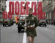 "A young woman in a customized military outfit marches at the head of a motorcade driving World War II veterans in downtown Moscow. The sign reads ""60 Years of Victory,"" in observance of Sunday&squot;s anniversary of the Allied powers&squot; victory over Nazi Germany in 1945."