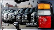 A line of full-size SUVs, vans and other trucks are reflected in the tailgate of a Chevrolet Suburban at a General Motors dealership in Glendale, Calif. Hulking SUVs have lost much of their muscle in both new- and used-vehicle markets.