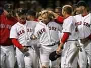Boston's Kevin Millar, center, is mobbed by teammates after belting a walk-off, two-run home run against Oakland. The Red Sox defeated the A's, 3-2, Tuesday night in Boston.