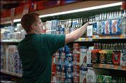 Mike Smith, grocery manager at Checkers Foods, 2300 La., stocks the store's beer sales area. Lawrence residents may soon be able to buy 3.2 beer on Sundays at grocery stores such as Checkers, plus convenience stores and other licensed retailers, thanks to a law set to be signed next week by Gov. Kathleen Sebelius.