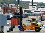 A shipping container is removed from an inbound tractor-trailer Wednesday in Seattle at the Port of Seattle. The U.S. trade deficit fell sharply in March to $54.99 billion, the lowest level in six months, as U.S. exports climbed to an all-time high.