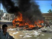 A car burns in the street as university students protest in the streets in Jalalabad, Afghanistany. Police and U.S. troops opened fire Wednesday in the eastern Afghan city to control hundreds of students rioting over alleged desecration of Islam's holy book at the U.S. jail in Guantanamo Bay, Cuba.