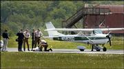 A Maryland State Police Trooper kneels over one of two people who were detained Wednesday at the Frederick, Md., Municipal Airport after flying in restricted airspace over Washington. The plane was forced to land at the airport by U.S. Air Force fighter jets and a U.S. Customs Blackhawk helicopter. The Frederick airport is about 50 miles from Washington.