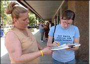 Charlotte Hastings, left, Lawrence, collects Lizz Conley's signature near Ninth and Massachusetts streets. Hastings and her mother, Keri Collins, pictured in background at left, solicited signatures Tuesday from people downtown in an effort to keep convicted sexual predator Leroy Hendricks and others like him from moving to town.