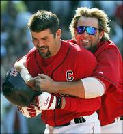 Boston's Jason Varitek, front, is congratulated by teammate Kevin Millar after hitting a game-winning home run against Oakland. The Red Sox defeated the A's, 6-5, Wednesday in Boston.