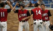 Lawrence High baseball players Will Falk (11) and John Novotny (14) high five Matt Falk and Nick Madl (12) after Falk and Madl scored against Free State High. The Lions were trailing the Firebirds, though, when Thursday night's game was suspended because of rain.