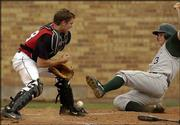 Lawrence High catcher Brett Sims, left, drops the ball, allowing Free State High's Cory Cooper to score.
