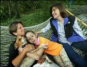 Hillary, left, and Julie Goodridge play with their 9-year-old daughter, Annie, and their dog, Mary, in their back yard in Boston. Julie and Hillary Goodridge were the lead plaintiffs in the lawsuit against the state of Massachusetts that led to same-sex marriages last year.