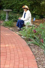 Gladys Staab sits on a bench smelling the aroma at the Audio-Reader sensory garden, 1120 W. 11th St., at Kansas University.