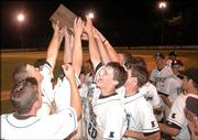 Free State High baseball players hold aloft the Class 6A regional championship trophy after a 14-13, eight-inning victory over Topeka High. Firebird Andy Petz (20) had the game-winning RBI on Thursday at Free State.